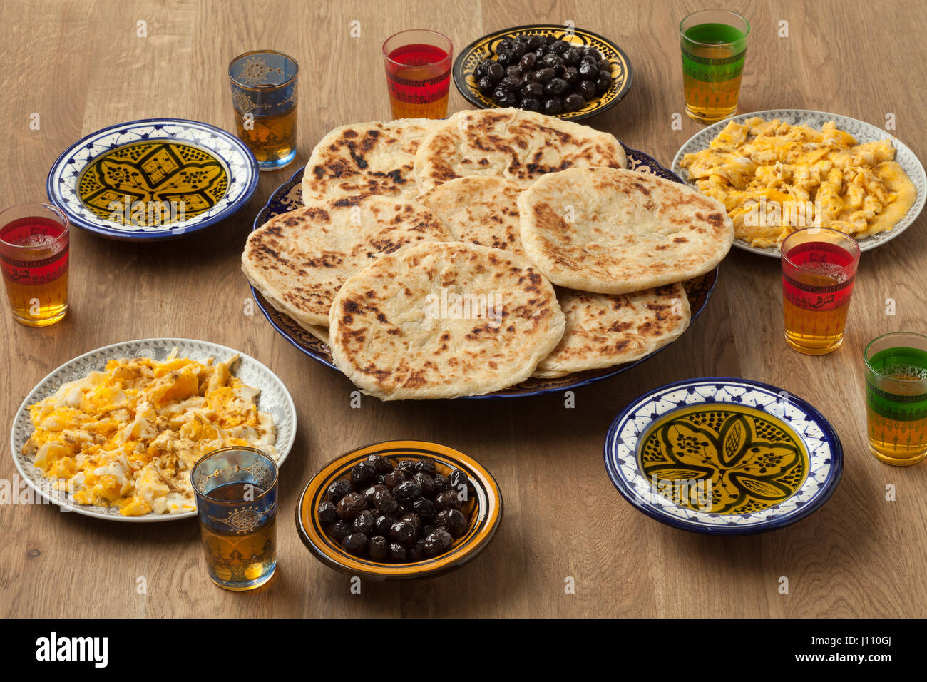 Traditional Moroccan  breakfast with pancakes,eggs,olives,olive oil and mint tea - Stock Image