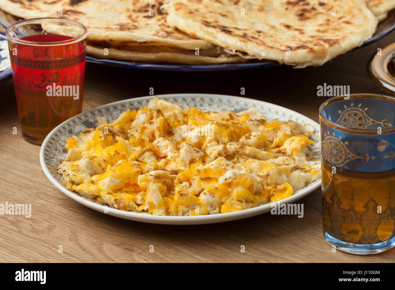 Traditional Moroccan  breakfast with scrambled eggs, pancakes and mint tea - Stock Image