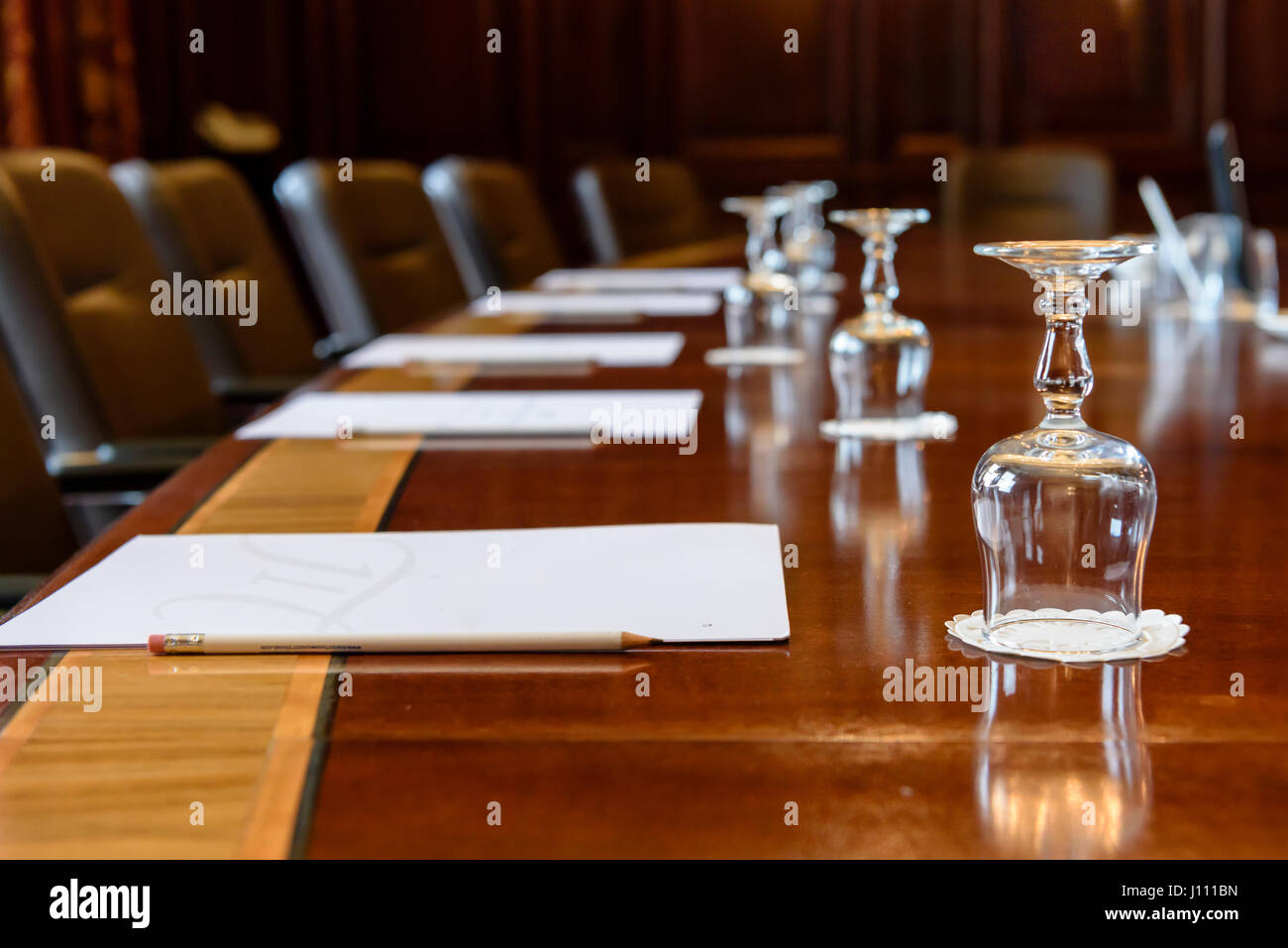 Large wooden table in a board room with wood panelling, set up for a meeting - Stock Image