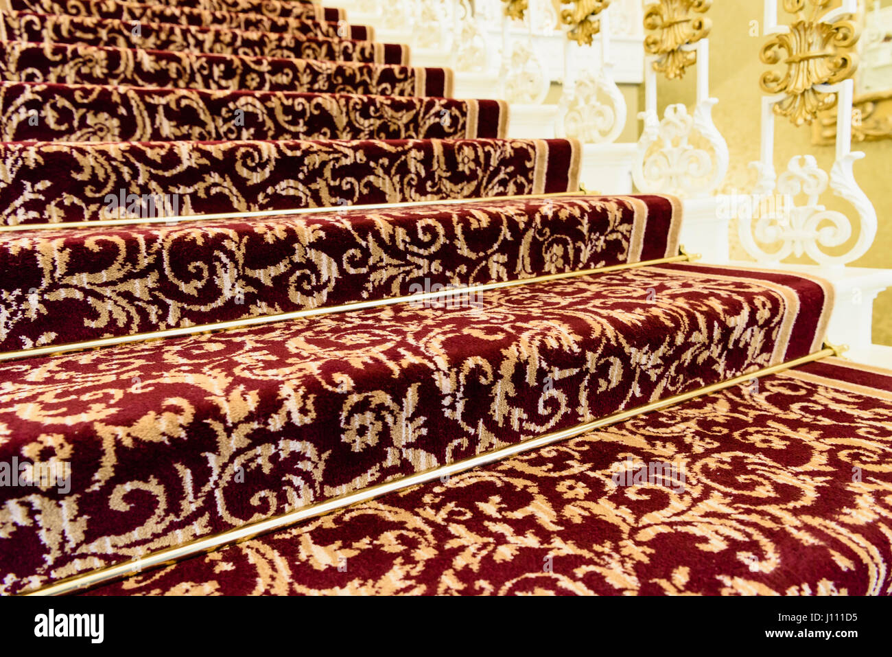 Brass Stairrods Holding Down Red Patterened Axminster Carpet On The Stairs  Of A Posh House.