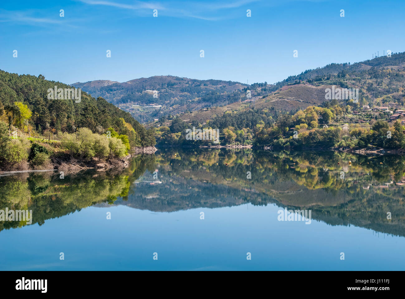 The water dam reflects the spring's sky and mountain colourfuness Stock Photo