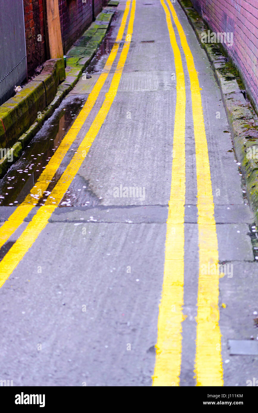 Double yellow lines down both sides of a very narrow road. - Stock Image