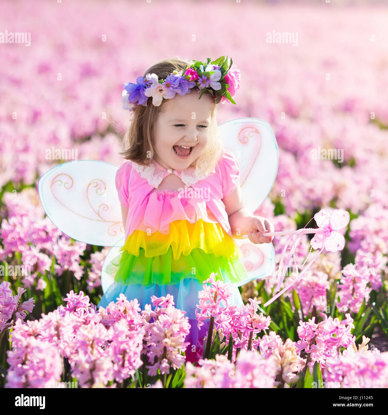 Superb Beautiful Girl Playing In Blooming Hyacinth Flower Field. Kids Princess  Birthday Party With Fairy Costume, Butterfly Wings And Magic Wand. Children  Pl