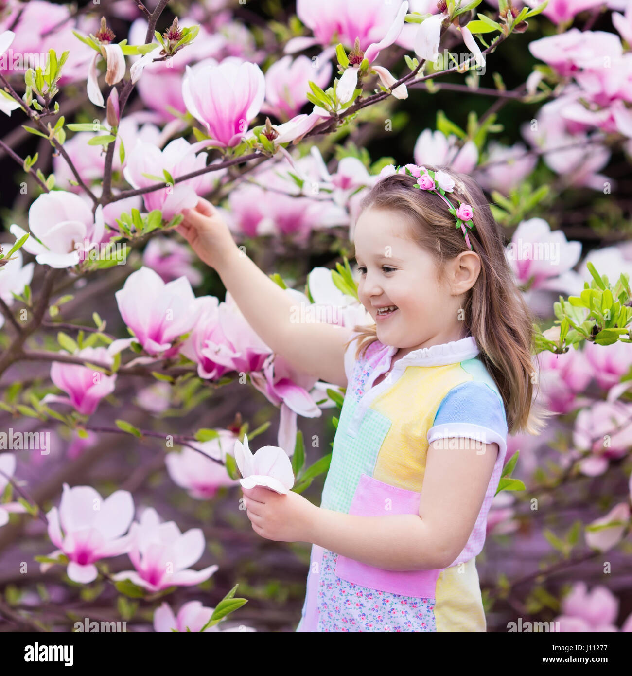 Happy little girl in pastel color dress and flower crown playing happy little girl in pastel color dress and flower crown playing under pink magnolia tree picking big flowers in blooming spring garden child with ma izmirmasajfo
