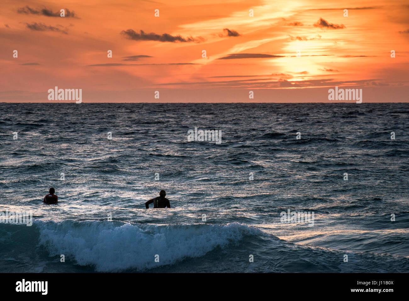 Surfing UK Surfers Waiting for a wave Sunset Intense sunset Fistral Cornwall Watersport Evening Physical activity - Stock Image