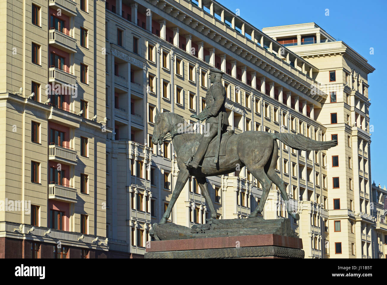 Moscow, Russia -February 18.2016. The monument to Marshal Zhukov on  background of  Four Seasons hotel Stock Photo