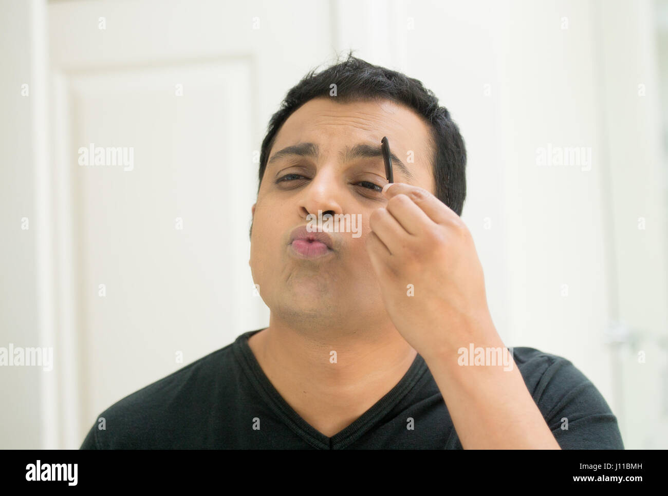 Closeup portrait, young handsome egotistical man in black t-shirt looking at mirror showing kisses and duck face, - Stock Image