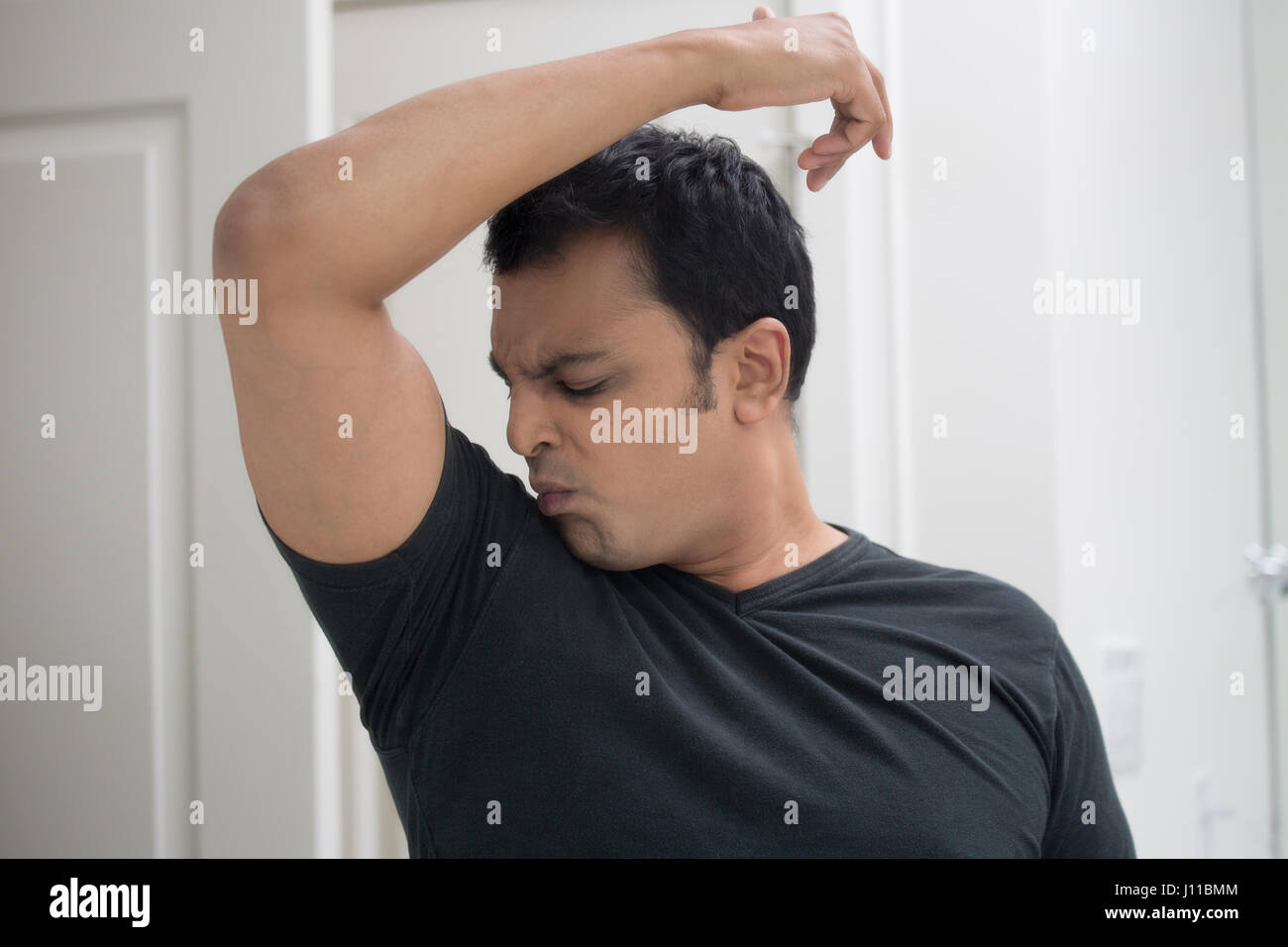 Closeup portrait, grumpy sweaty young man in black t-shirt, sniffing himself, very foul situation, isolated mirror - Stock Image