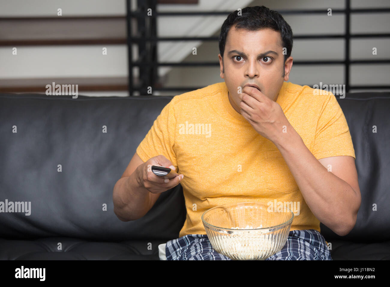 Closeup portrait, young man in yellow t-shirt, sitting on black leather couch, watching TV, holding remote, surprised - Stock Image