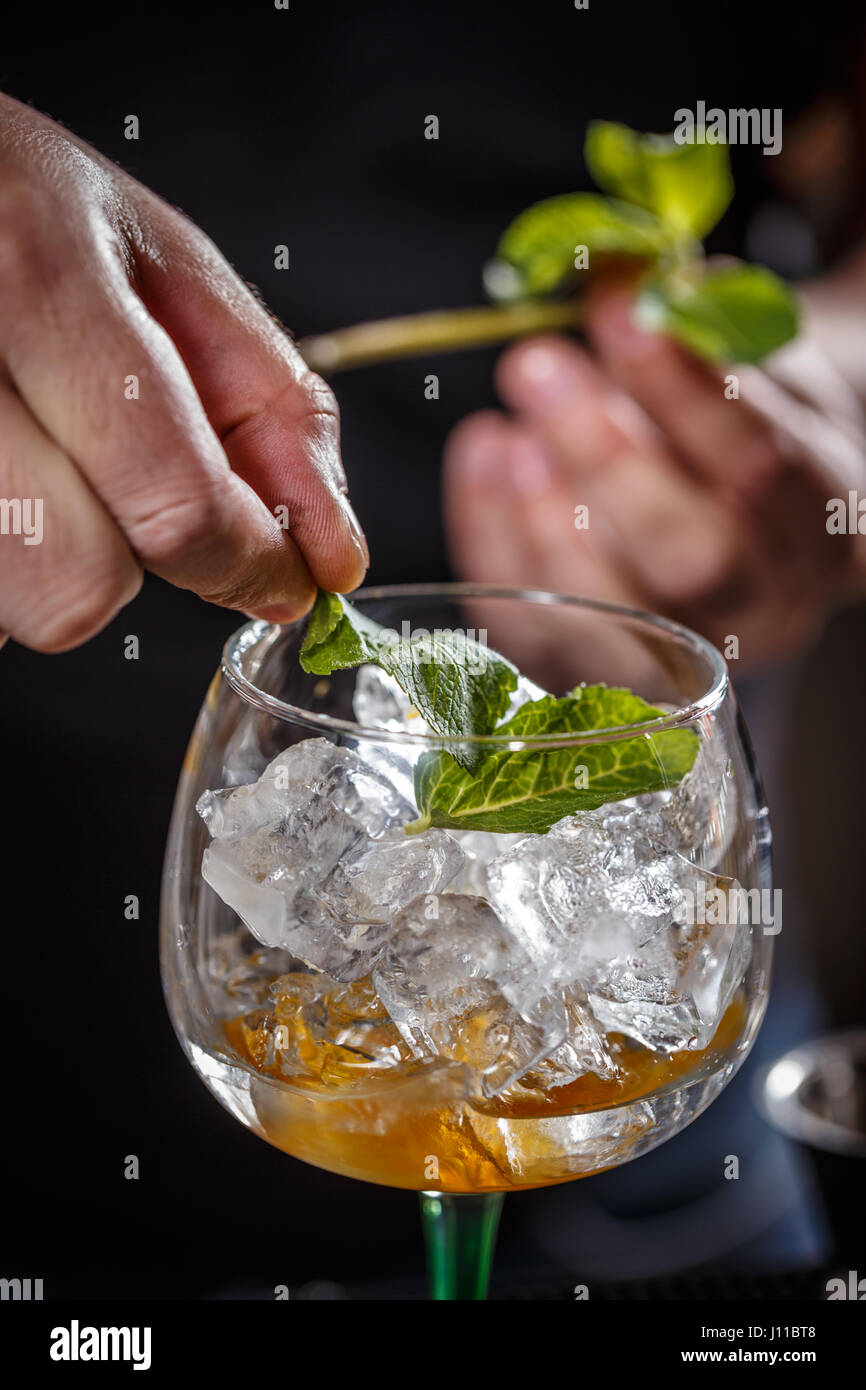 Barman is decorating cocktail with mint - Stock Image