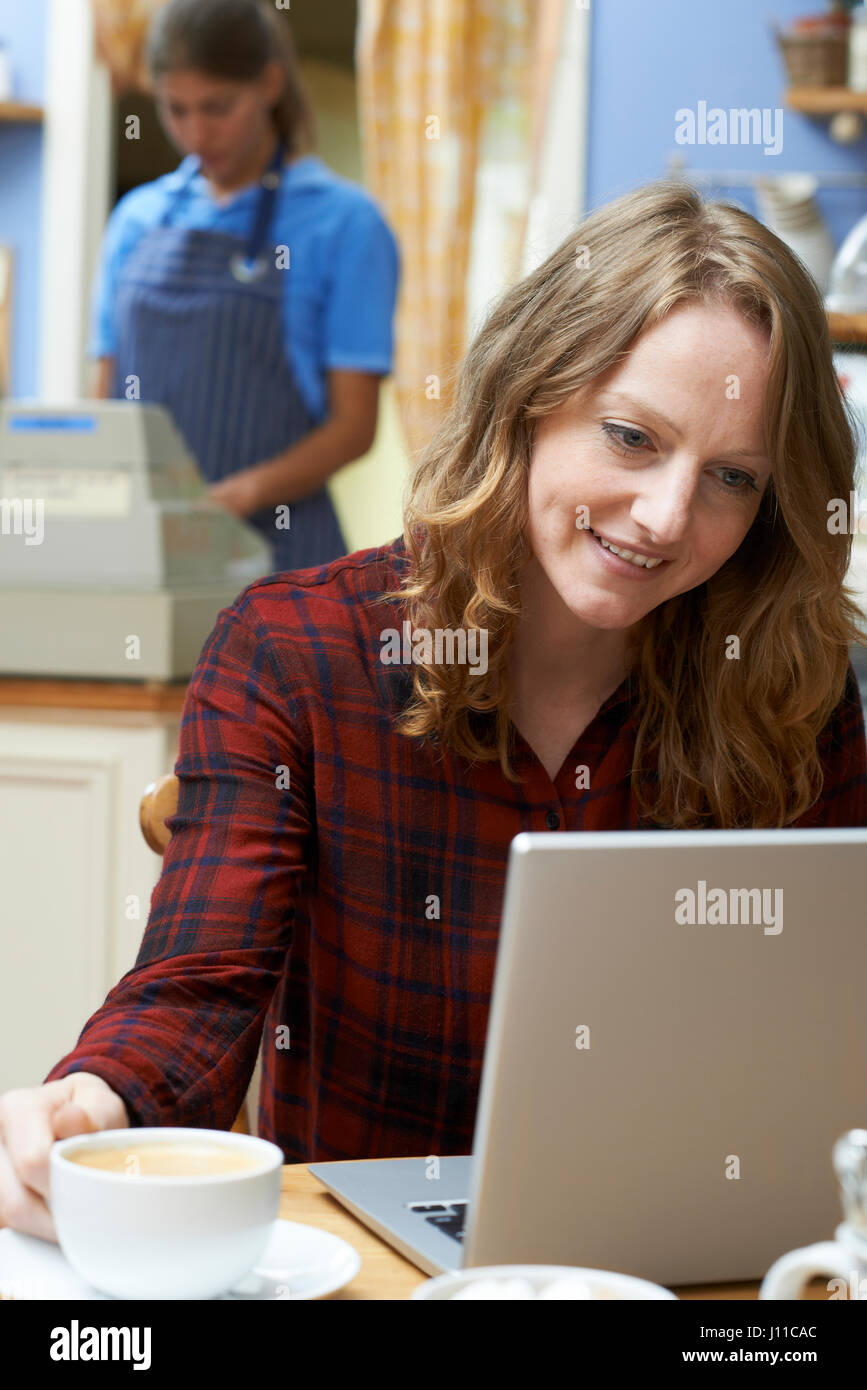 Woman In Coffee Shop Using Laptop Computer - Stock Image