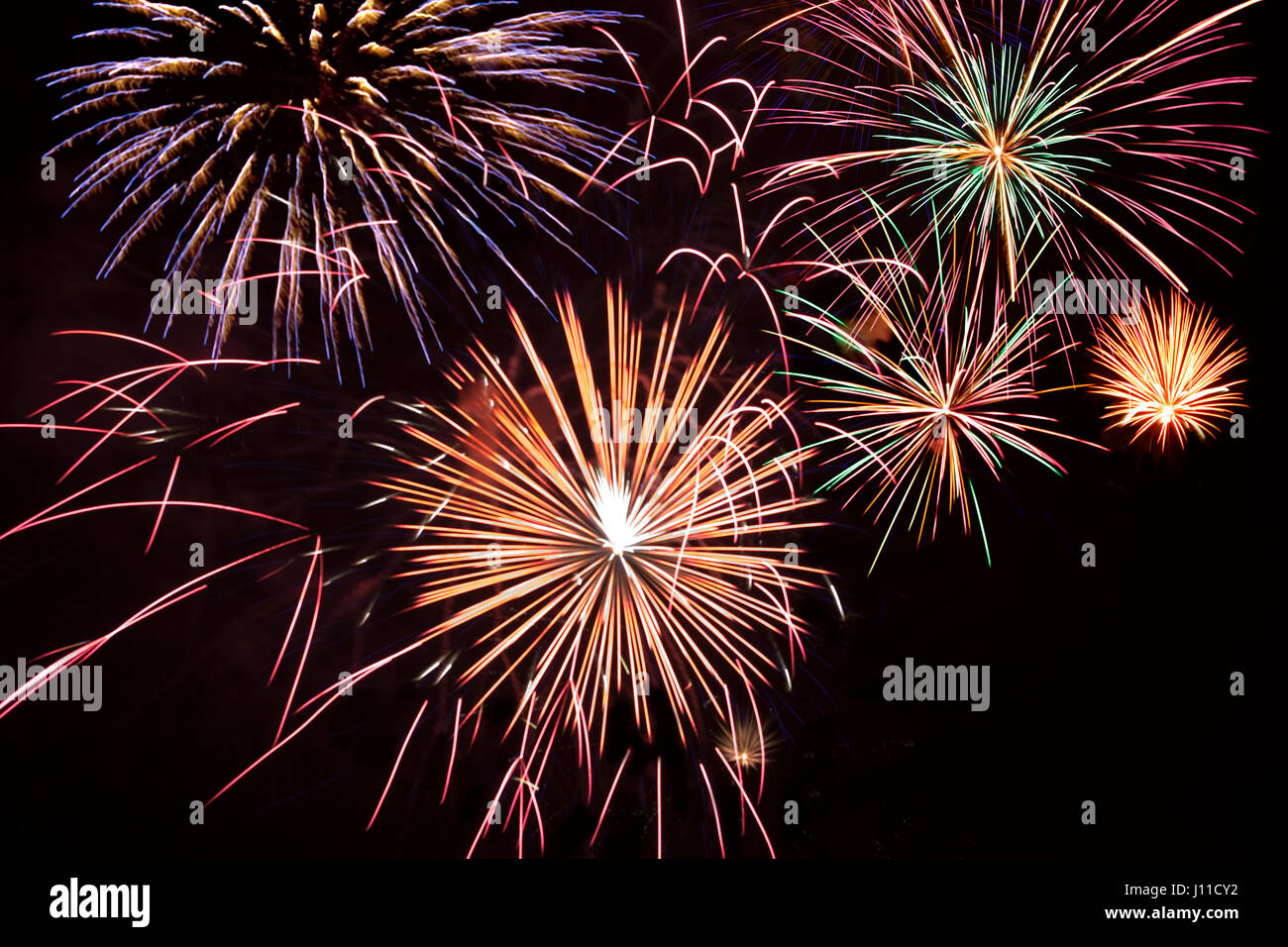 MULTIPLE SMOKELESS FIREWORK BURSTS ON CLEAR BLACK SKY - Stock Image