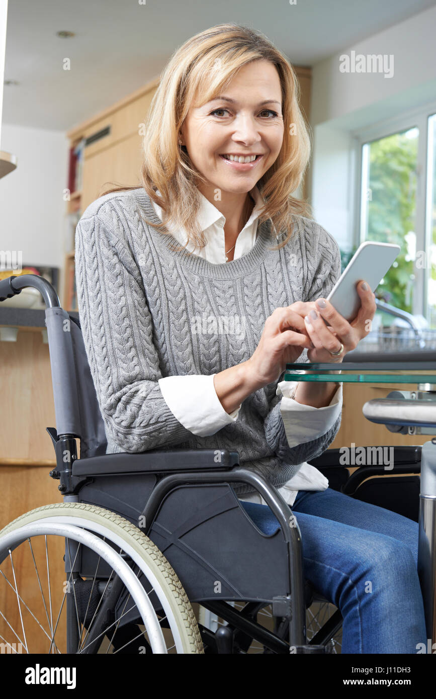 Disabled Woman In Wheelchair Texting On Mobile Phone At Home - Stock Image