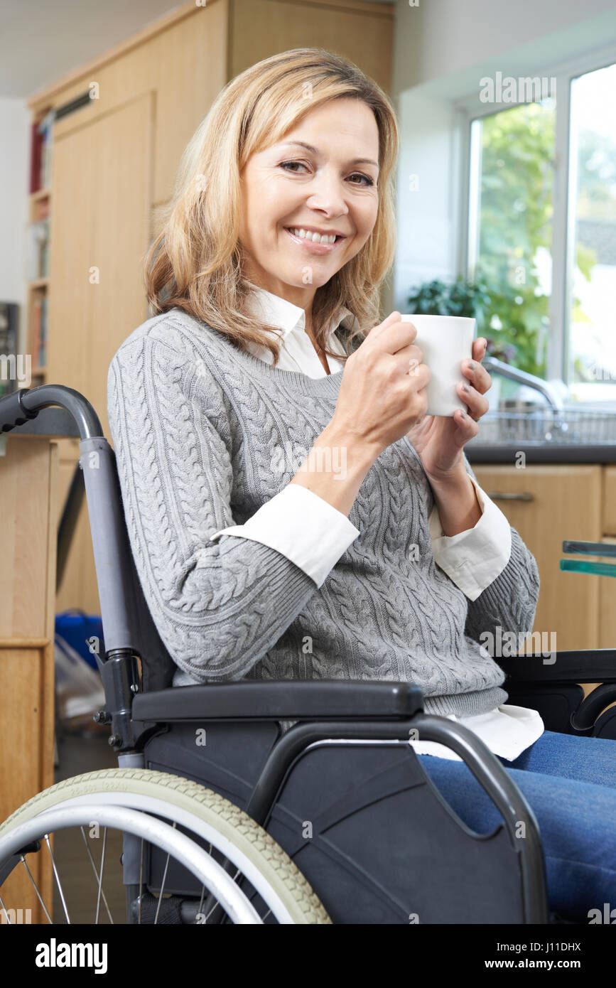 Disabled Woman Sitting In Wheelchair At Home With Hot Drink - Stock Image