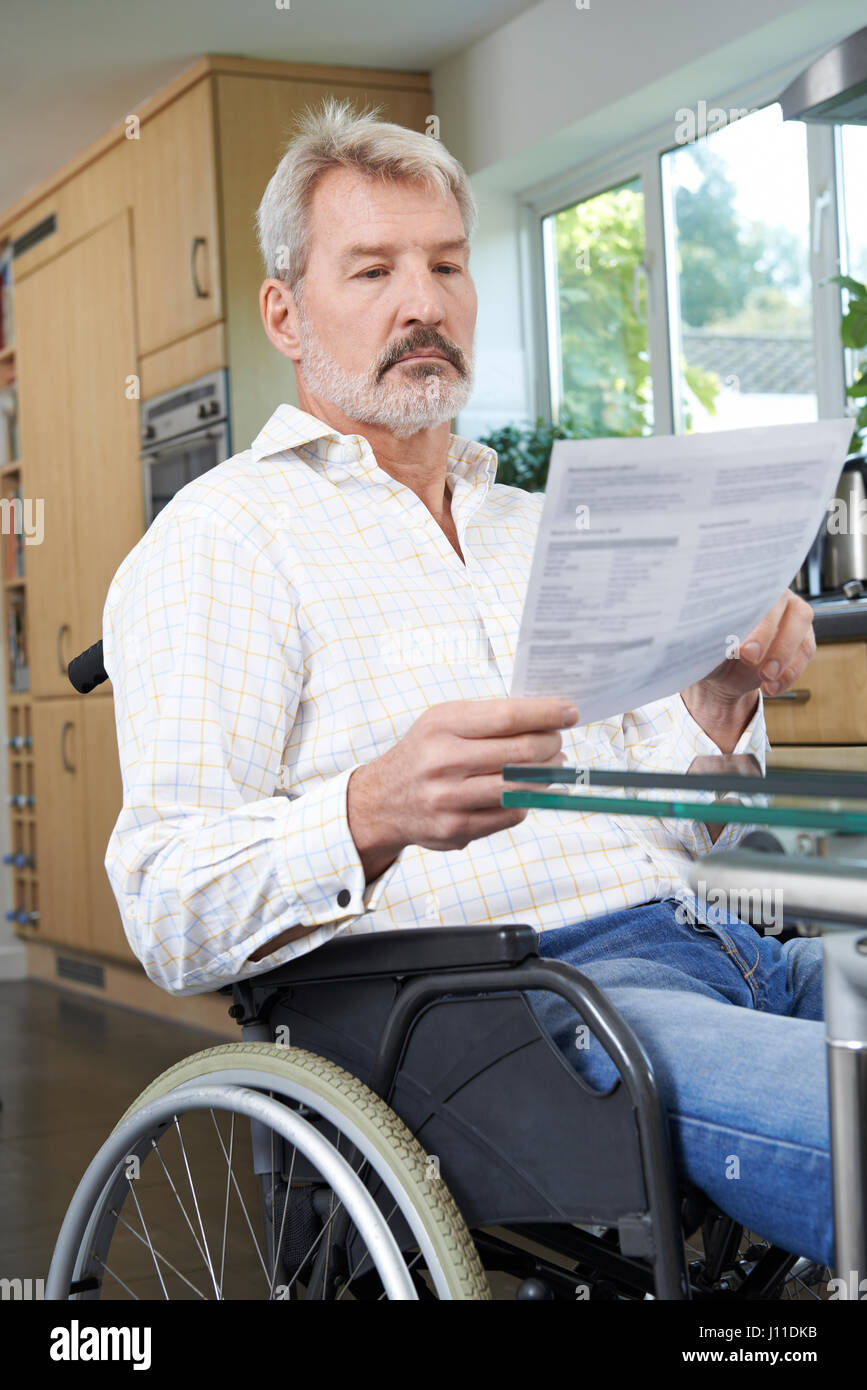 Frustrated Man In Wheelchair At Home Reading Letter - Stock Image