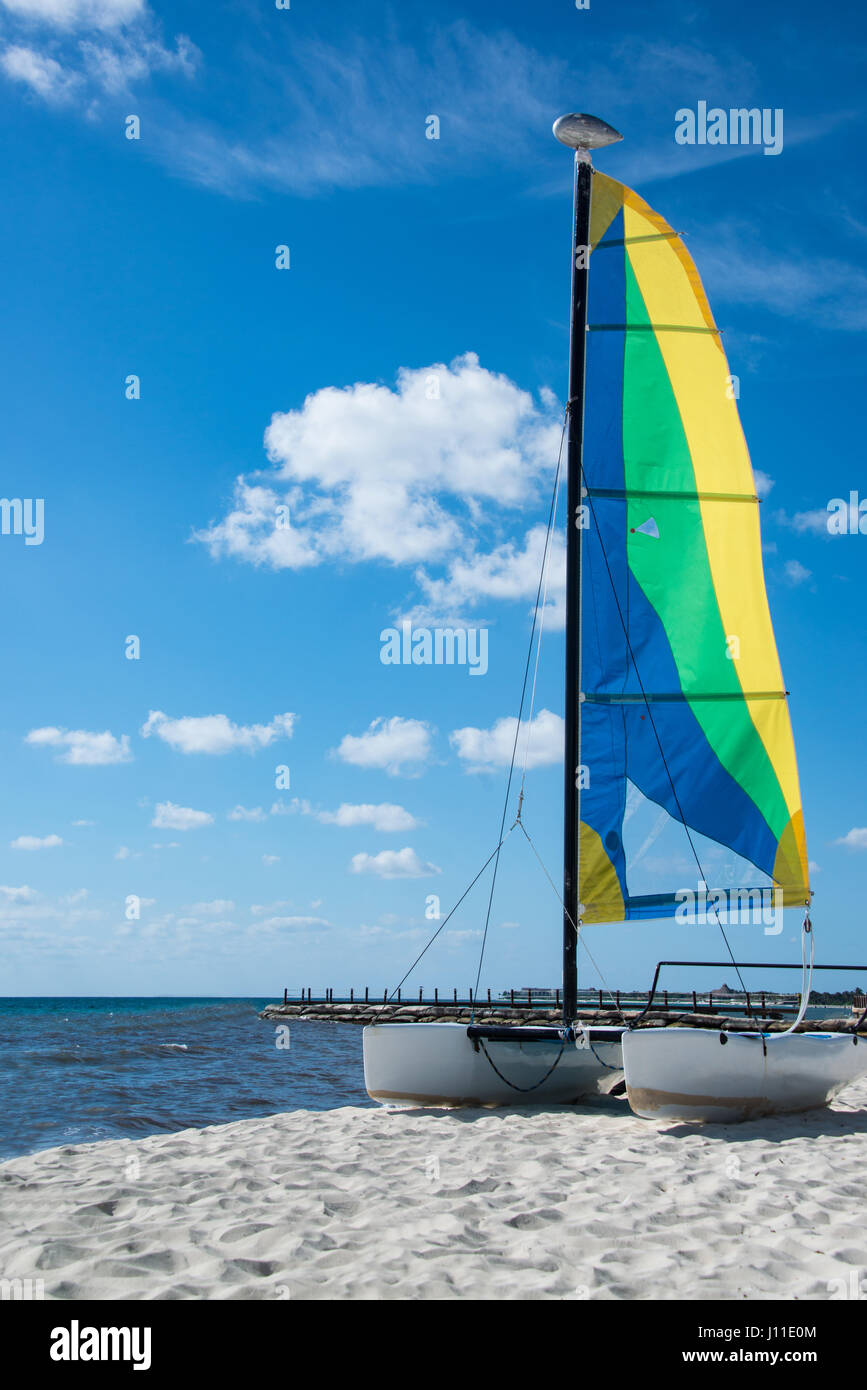 Colorful sail and sailboat catamaran is pulled up and docked on sandy beach in Mexican Caribbean on a bright sunny Stock Photo
