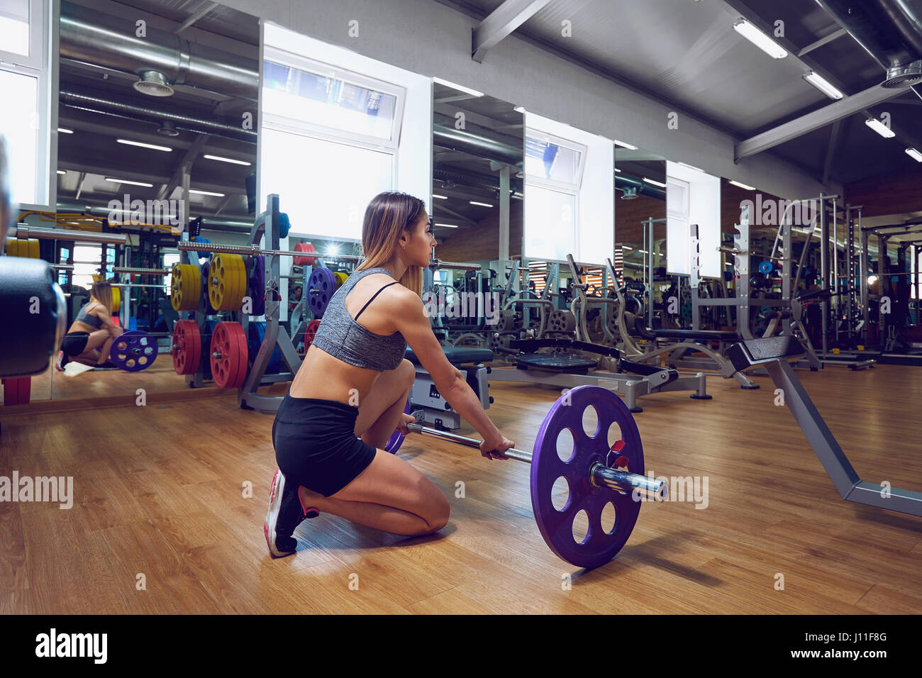 Girl with a barbell in the gym. - Stock Image