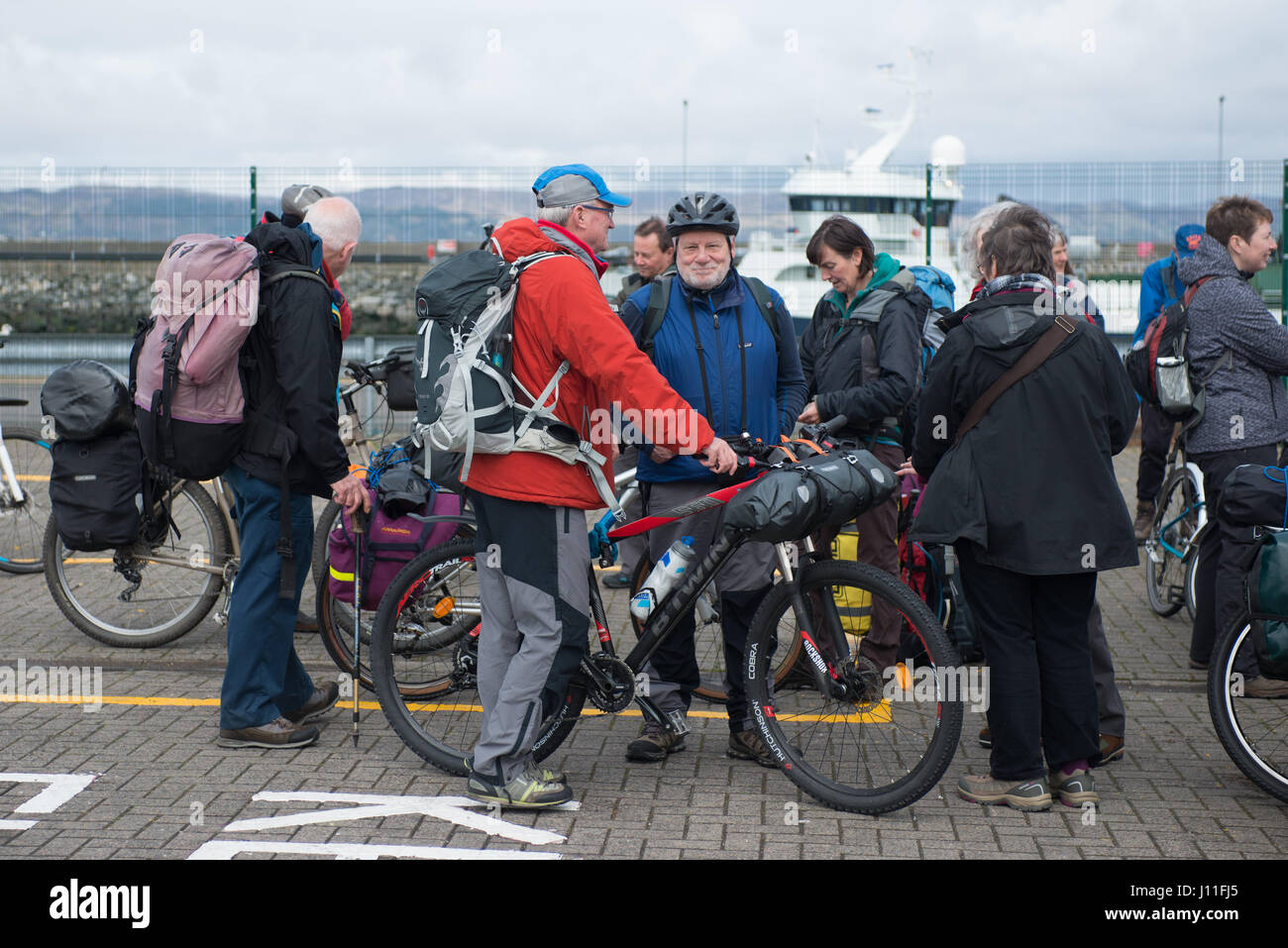 Cyclist waiting to board the Cal Mac Ferry Lochnevis to the Islands of Rum and Canna - Stock Image