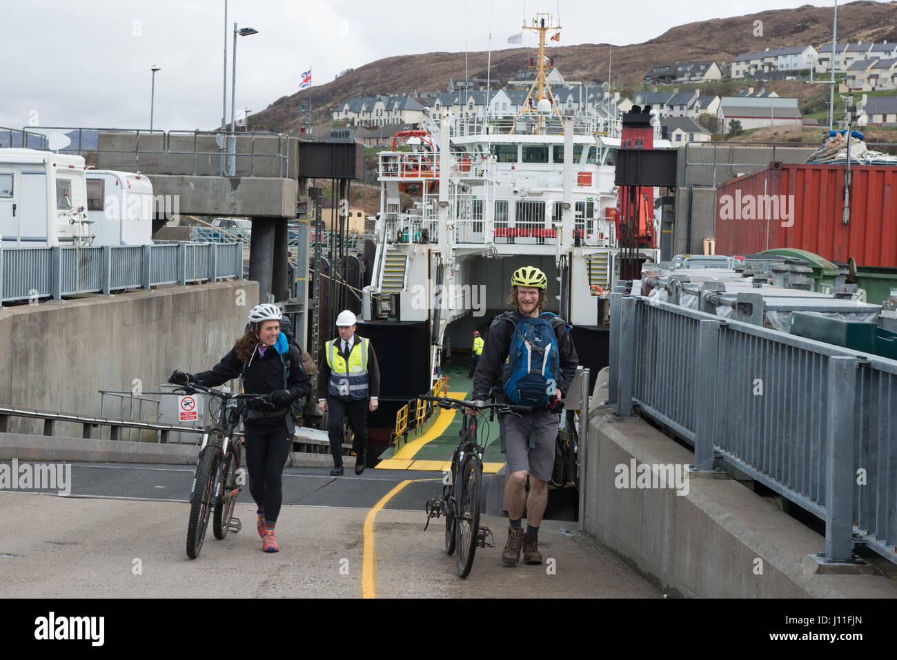 Cyclist disembarking the Cal Mac Ferry Lochnevis from Islands of Rum and Canna - Stock Image