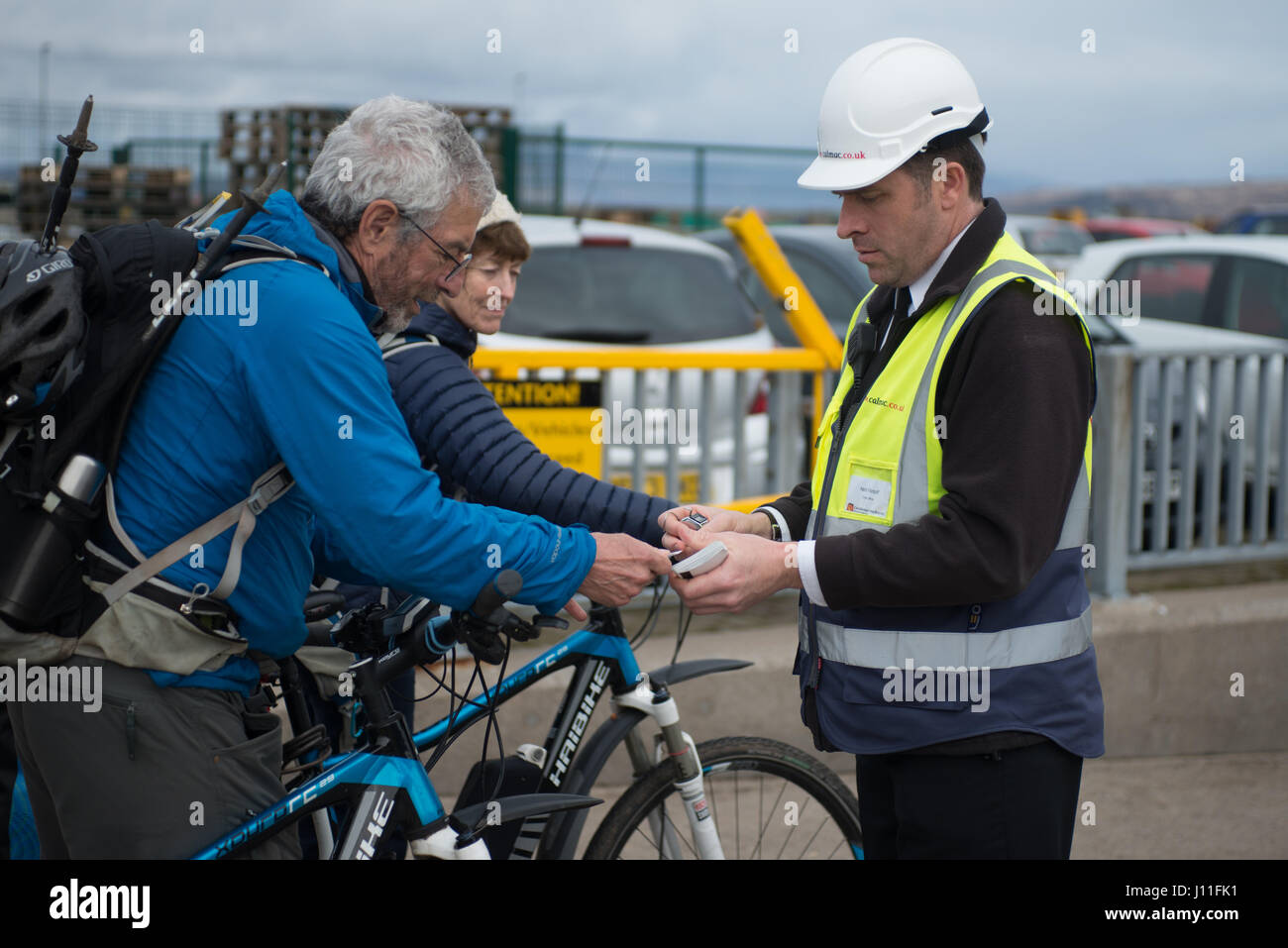 Cyclist showing ticket to board the Cal Mac Ferry Lochnevis to the Islands of Rum and Canna - Stock Image