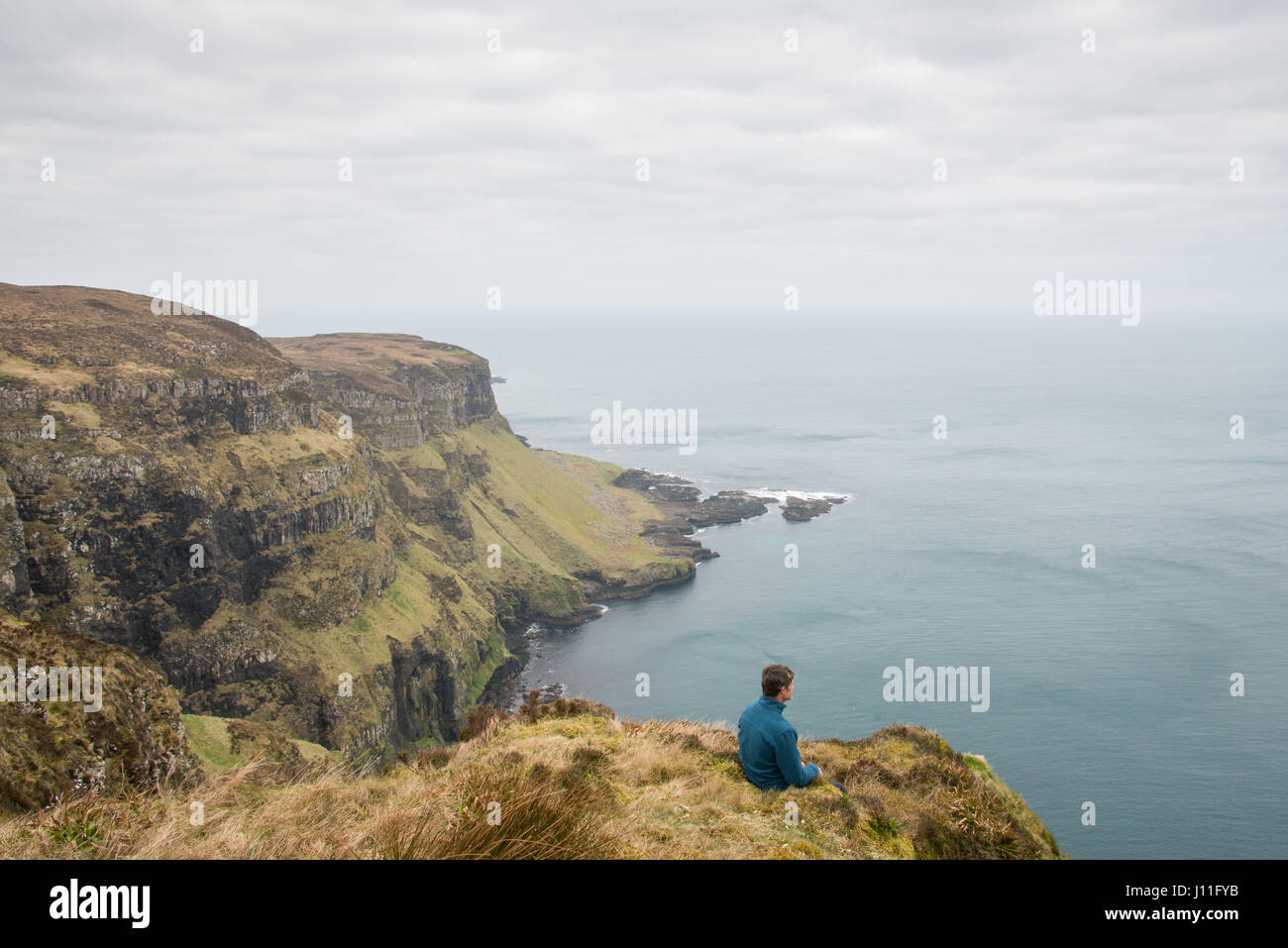 Admiring the view from Cliffs on the north coast of the Island of Canna, inner hebrides, Scotland. - Stock Image