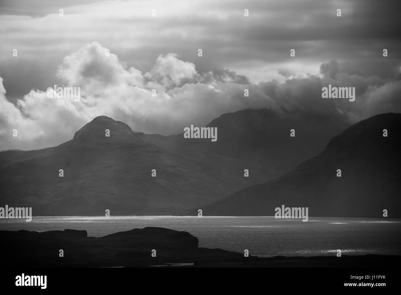 Clouds and mist over the island of Rum viewed from Canna Island, inner hebrides, Scotland - Stock Image