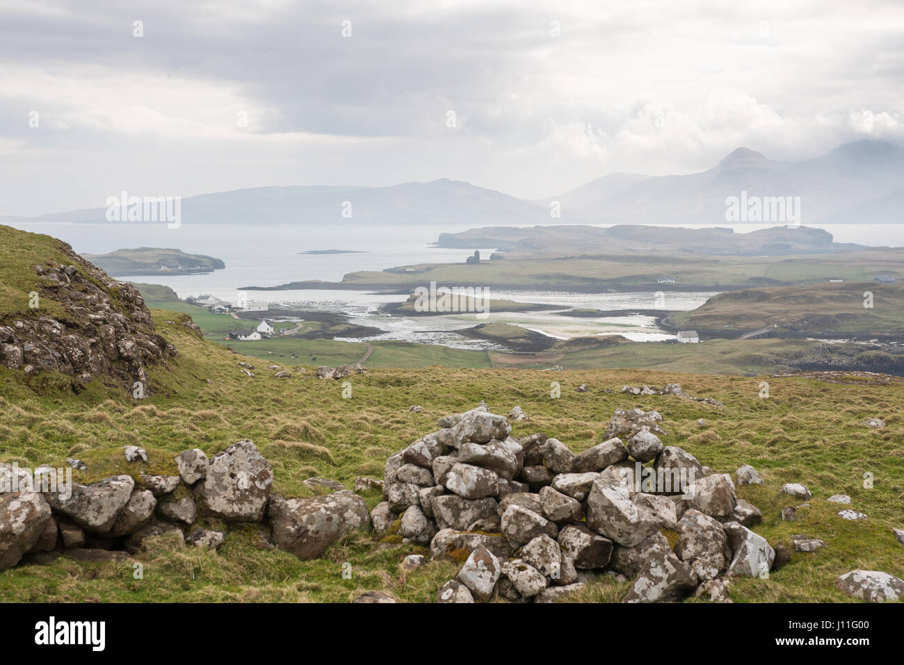 View from Canna Island of isolated houses and the island of Sanday. Inner Hebrides, Scotland - Stock Image