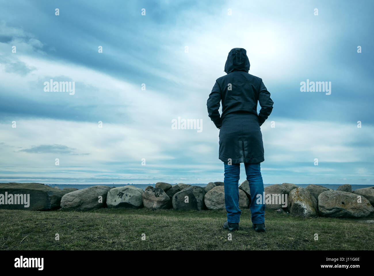 Lonely hooded female person from behind standing at seashore and looking into distance on a cold winter day, concept - Stock Image