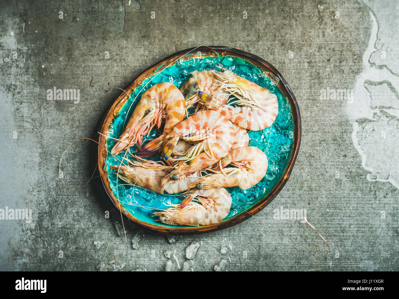 Raw uncooked tiger prawns on chipped ice, copy space - Stock Image