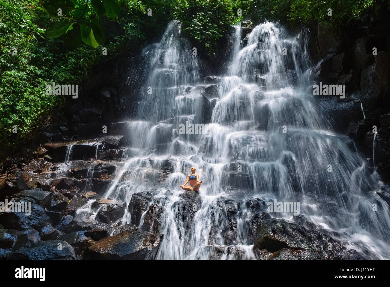Travel in Bali jungle. Beautiful young woman sit in zen-like yoga pose under falling spring water, enjoy tropic - Stock Image
