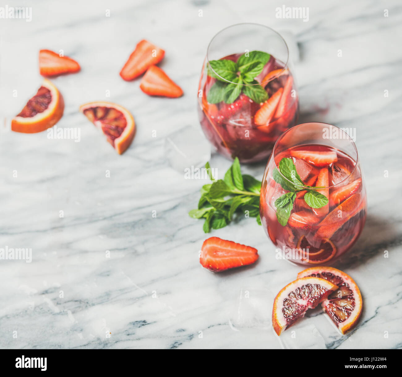 Fruit refreshing Sangria cocktails with ice and fresh mint - Stock Image