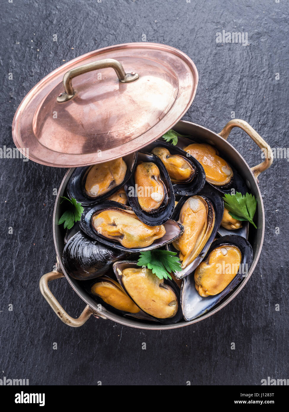 Boiled mussels in copper pan on the graphite background. - Stock Image