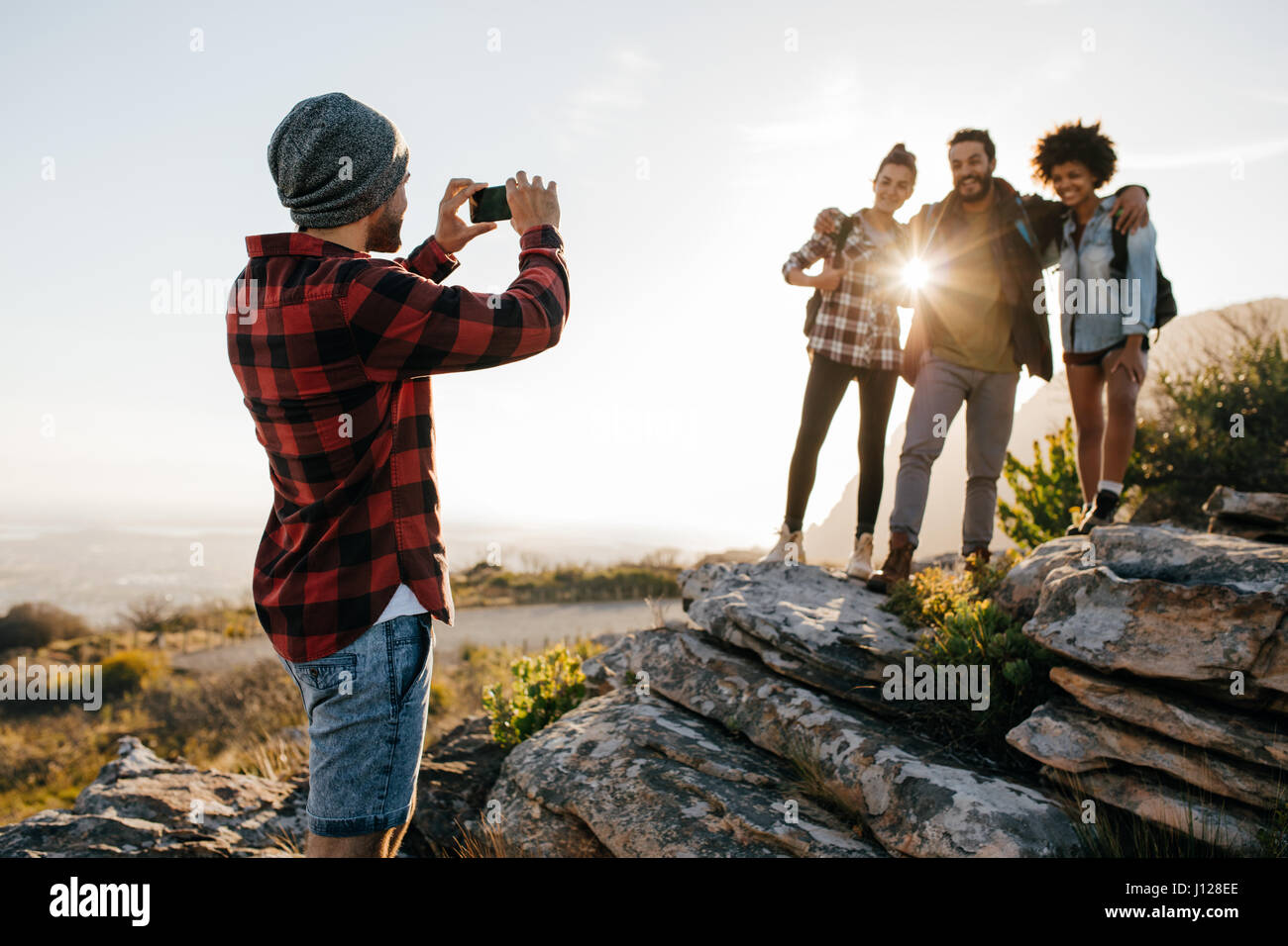 Group of friends standing outdoors taking picture by smartphone. Young people on mountain hike taking photographs. - Stock Image
