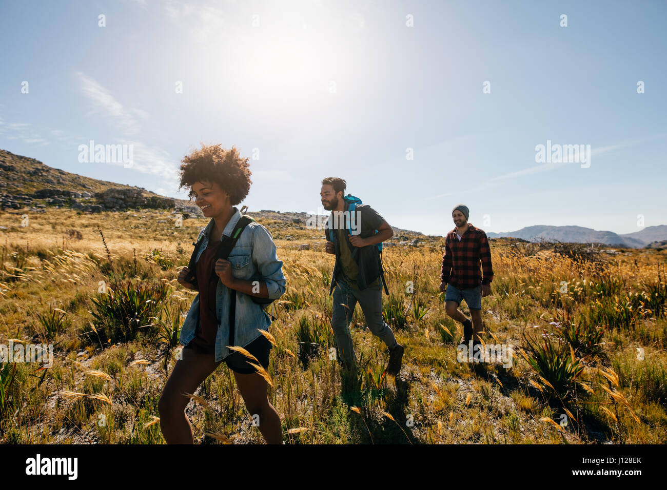 Group of people on walk through countryside. Happy young men and women hiking together on a summer day. - Stock Image