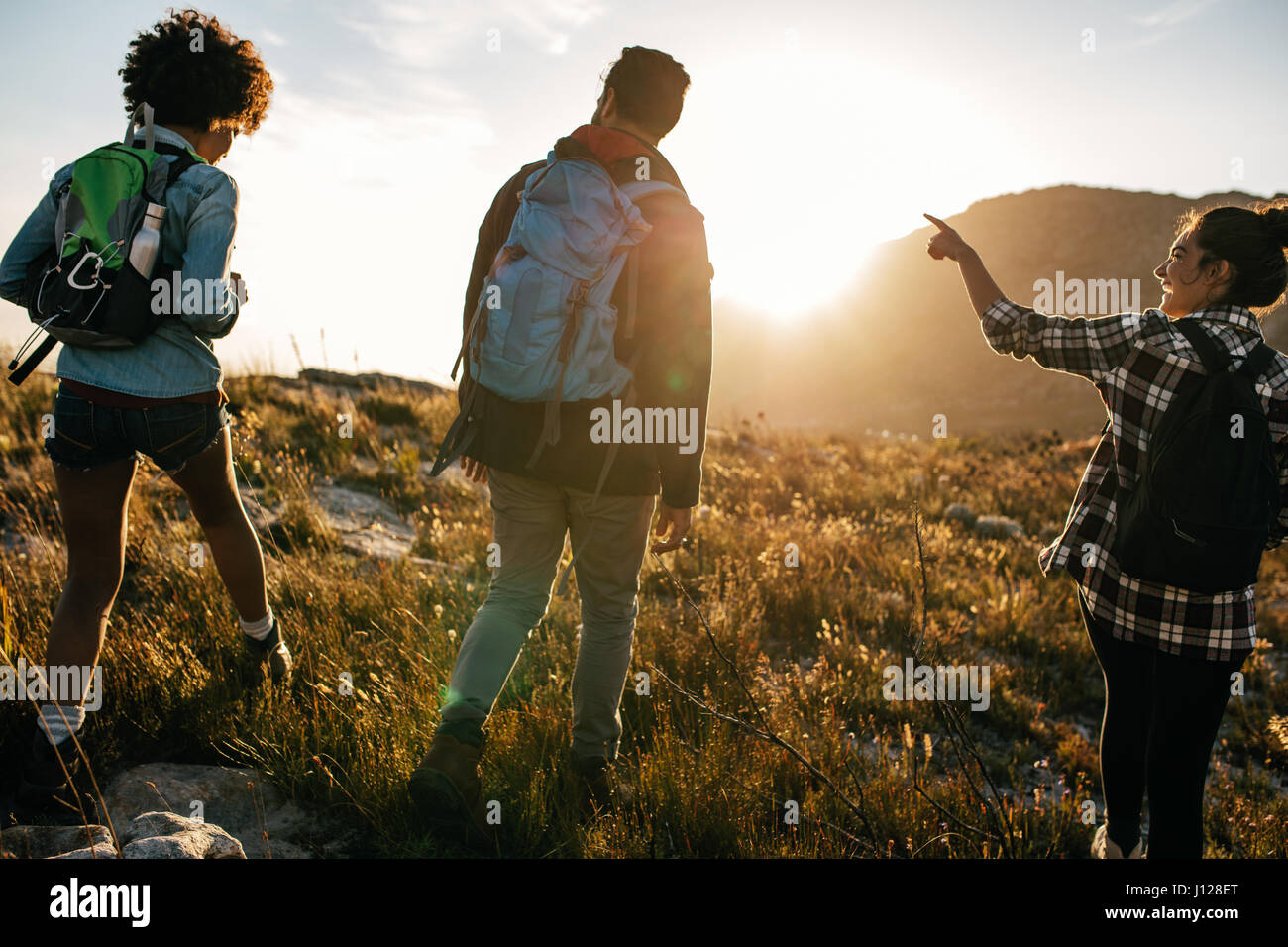Rear view shot of young people on countryside hiking. Group of hikers walking on hill on a summer day. - Stock Image