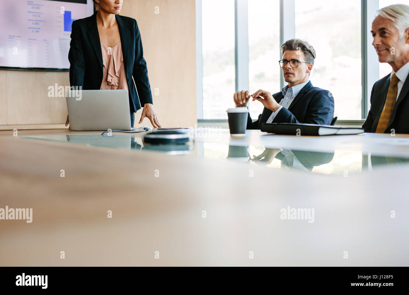 Businesspeople sitting at board room and discussing new strategies. Businessman and businesswoman meeting in conference - Stock Image