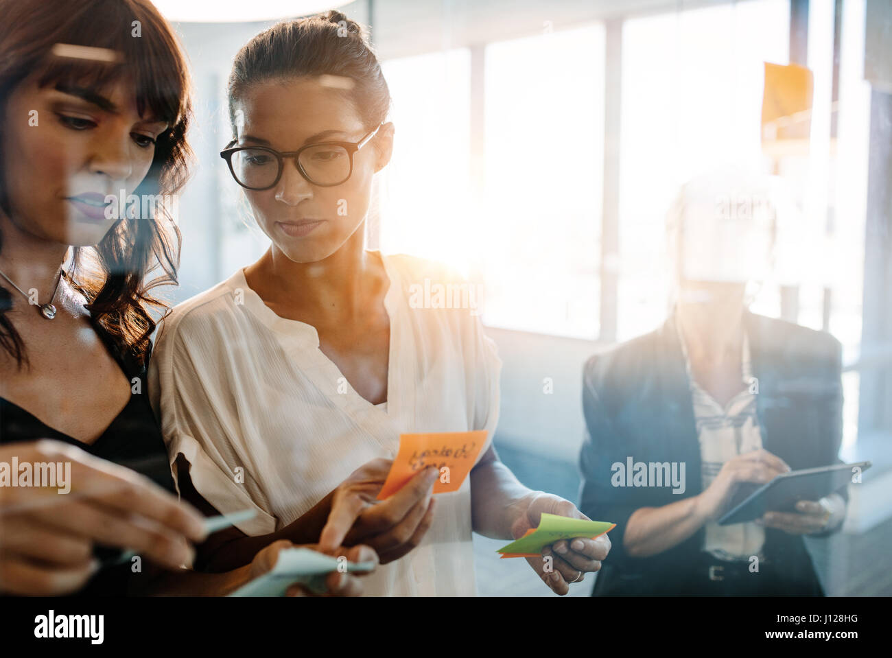 Business women discussing in front of glass wall using post it notes and stickers. Corporate professionals using - Stock Image