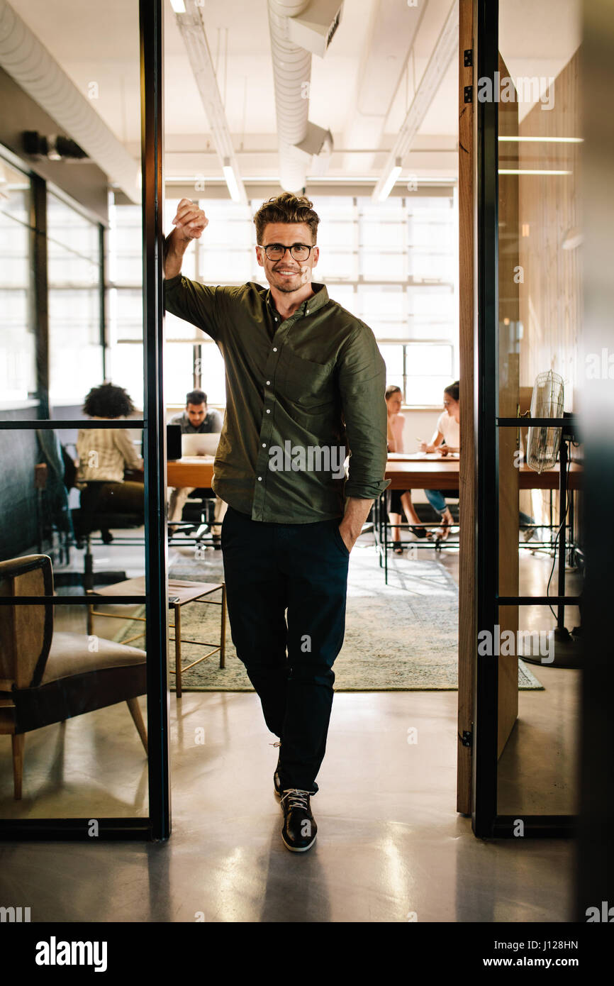 Full length portrait of happy young businessman standing in doorway of office. Caucasian male executive in office - Stock Image