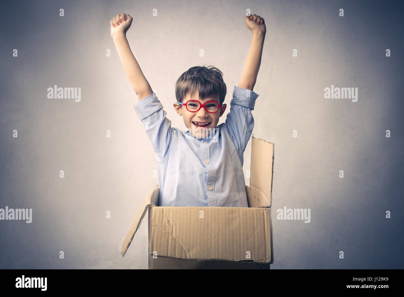 Little boy coming out of box - Stock Image