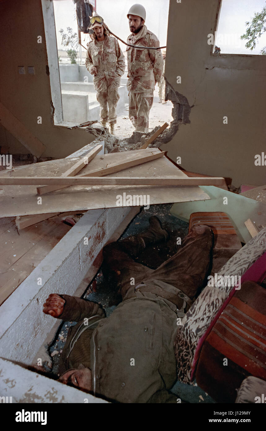 Saudi soldiers peer into a destroyed building at a killed Iraqi Republican guard following the Battle of Khafji - Stock Image