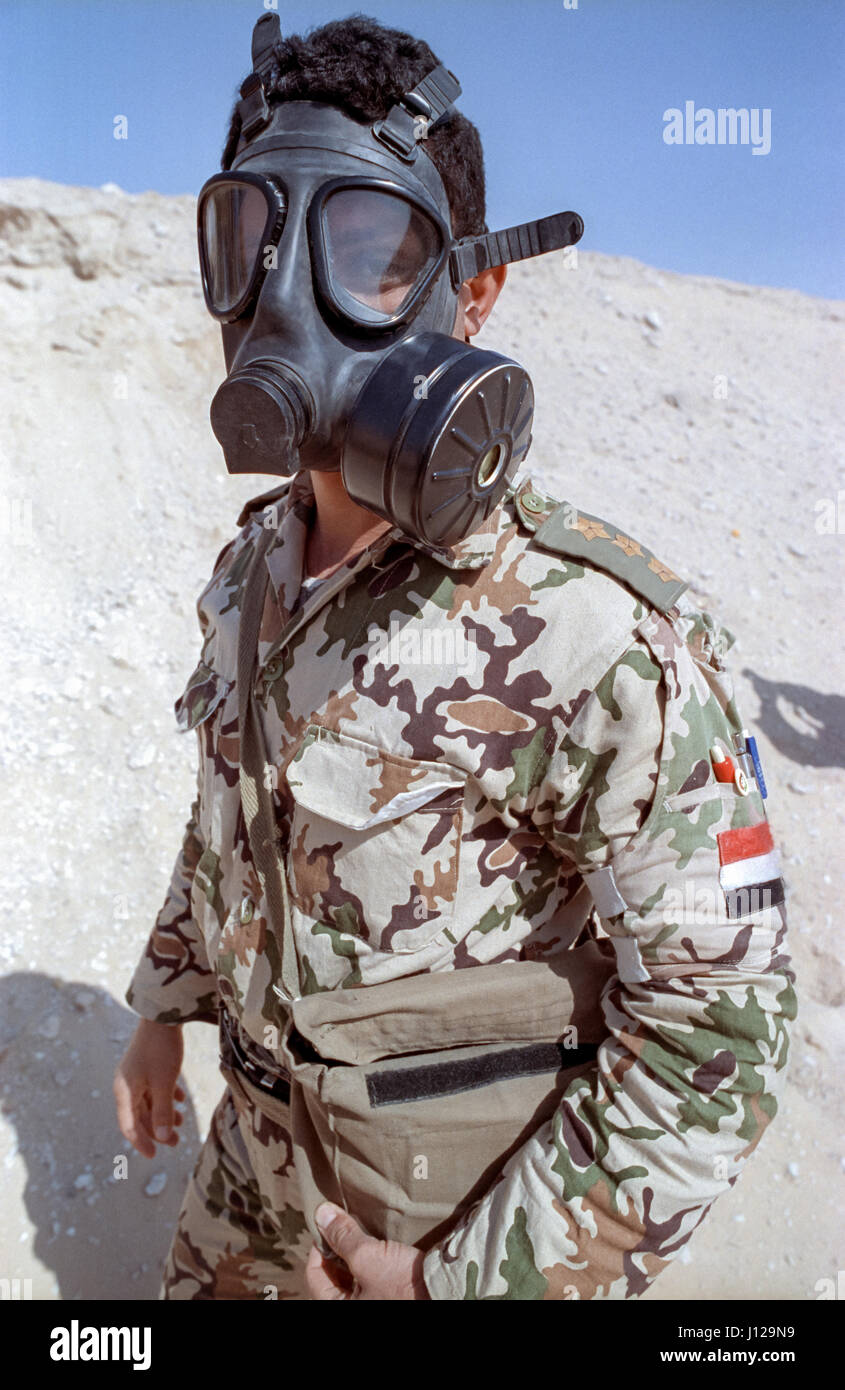 An Egyptian soldier wears a gas mask during a chemical weapons drill along the sand berm frontline border wall separating - Stock Image