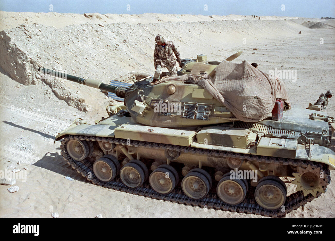 An Egyptian soldier positions a M60 battle tank along the sand berm border wall on the frontline separating Kuwait - Stock Image