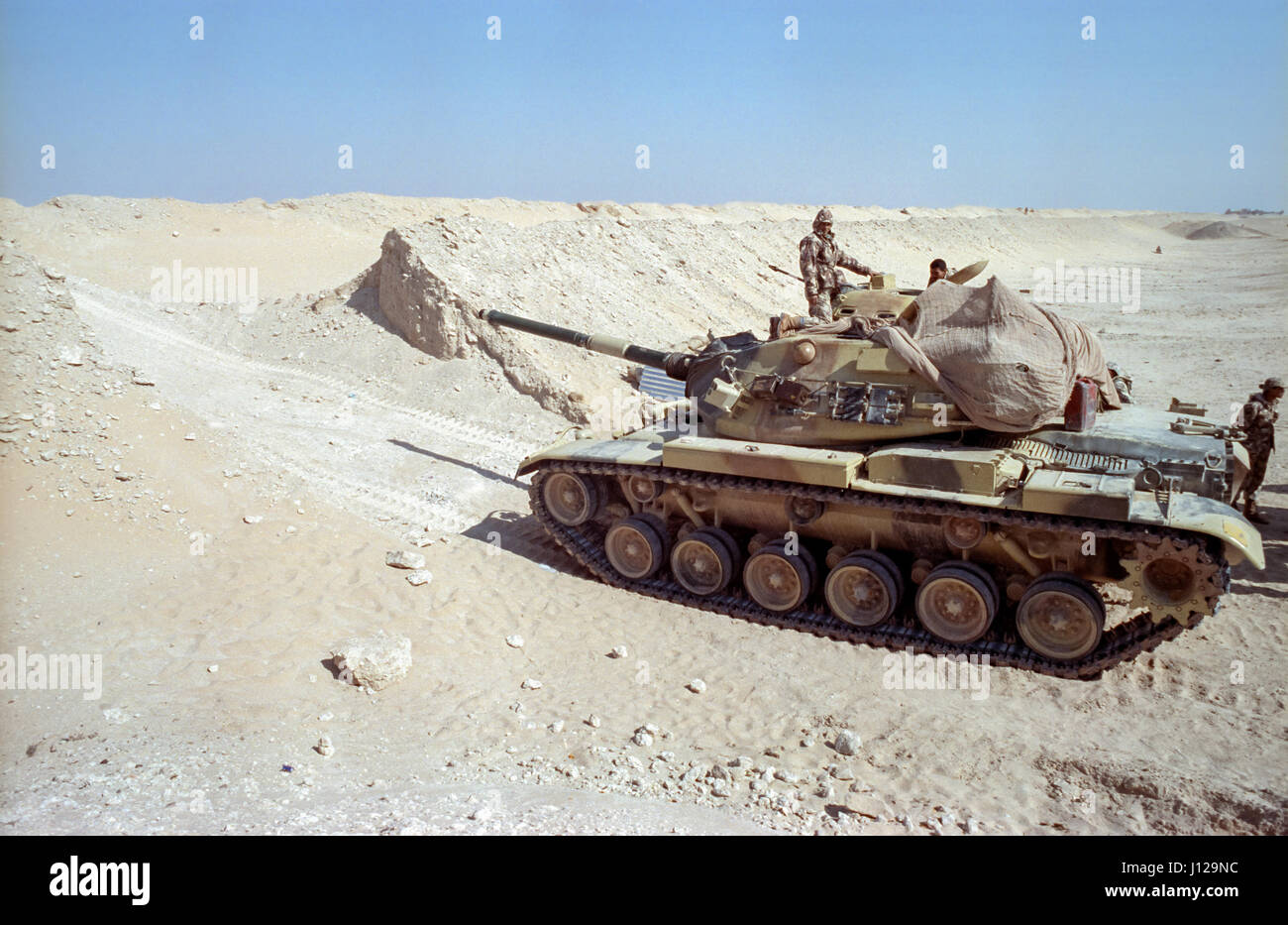 Egyptian soldiers positions a M60 battle tank along the sand berm border wall on the frontline separating Kuwait - Stock Image