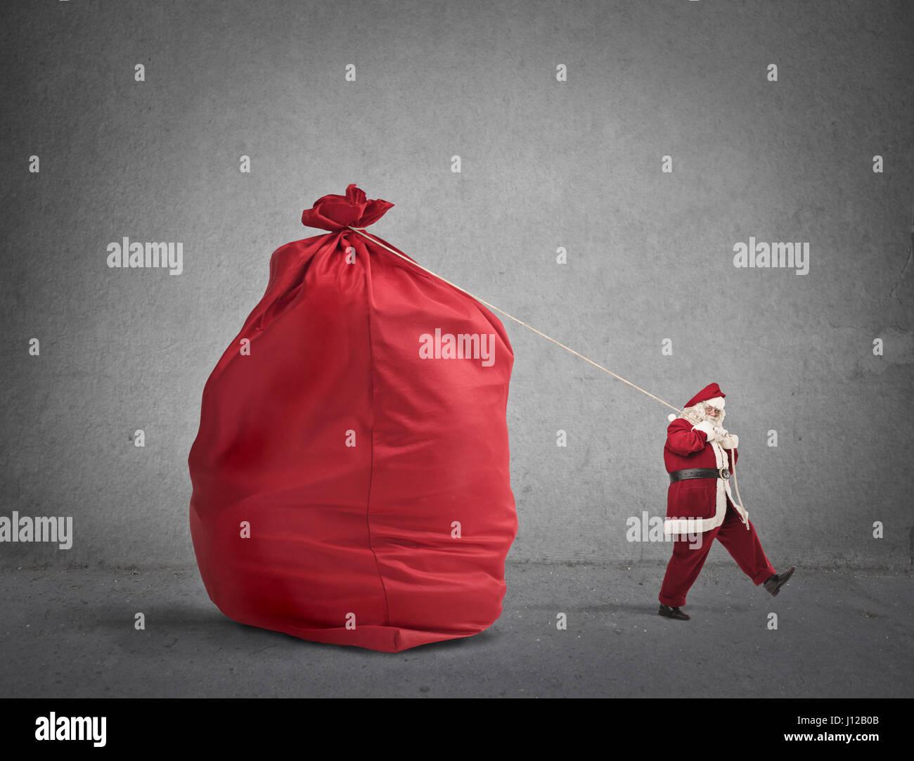Santa pulling huge bag - Stock Image