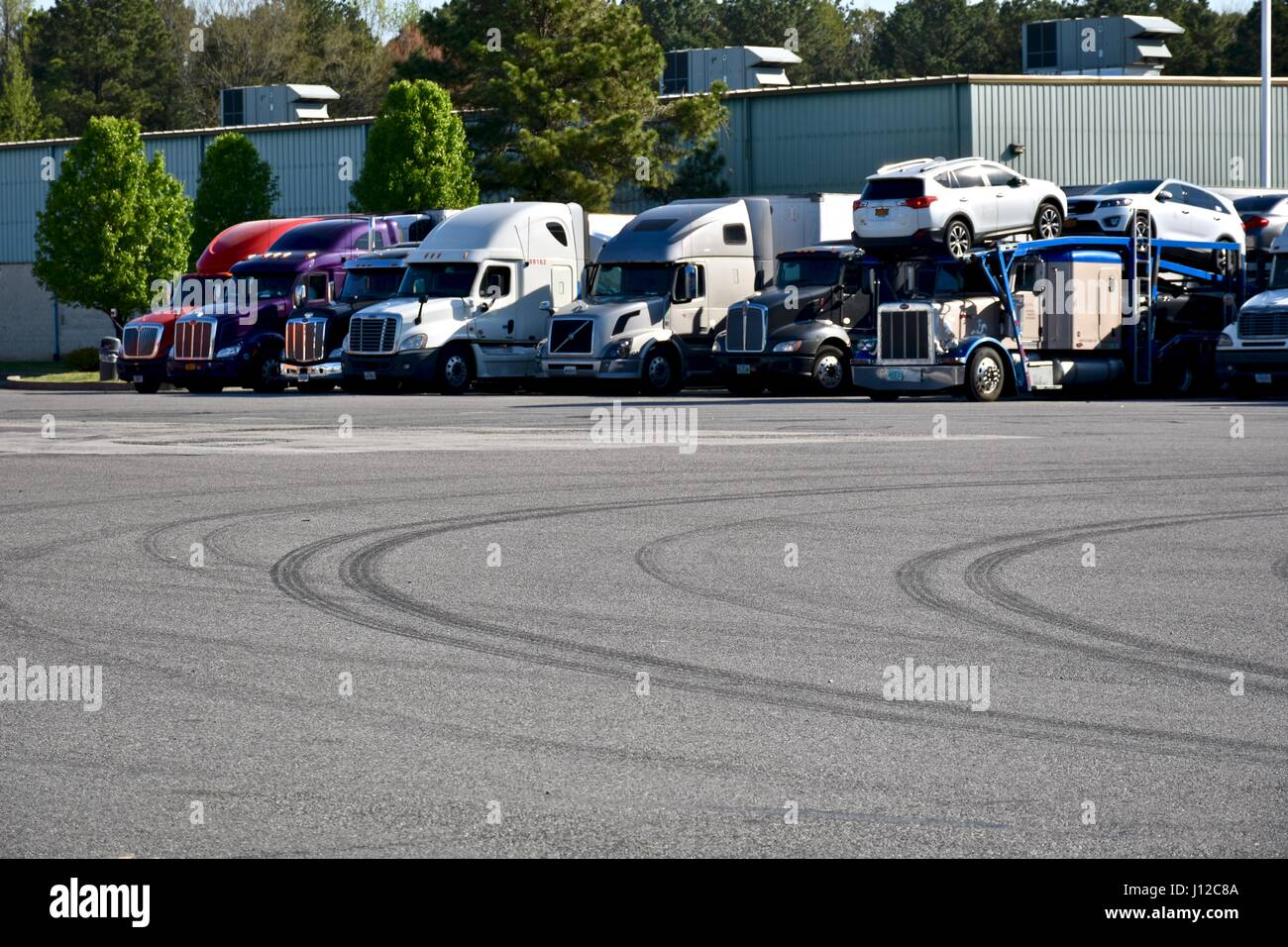 Long-haul semi trucks parked at truck stop - Stock Image