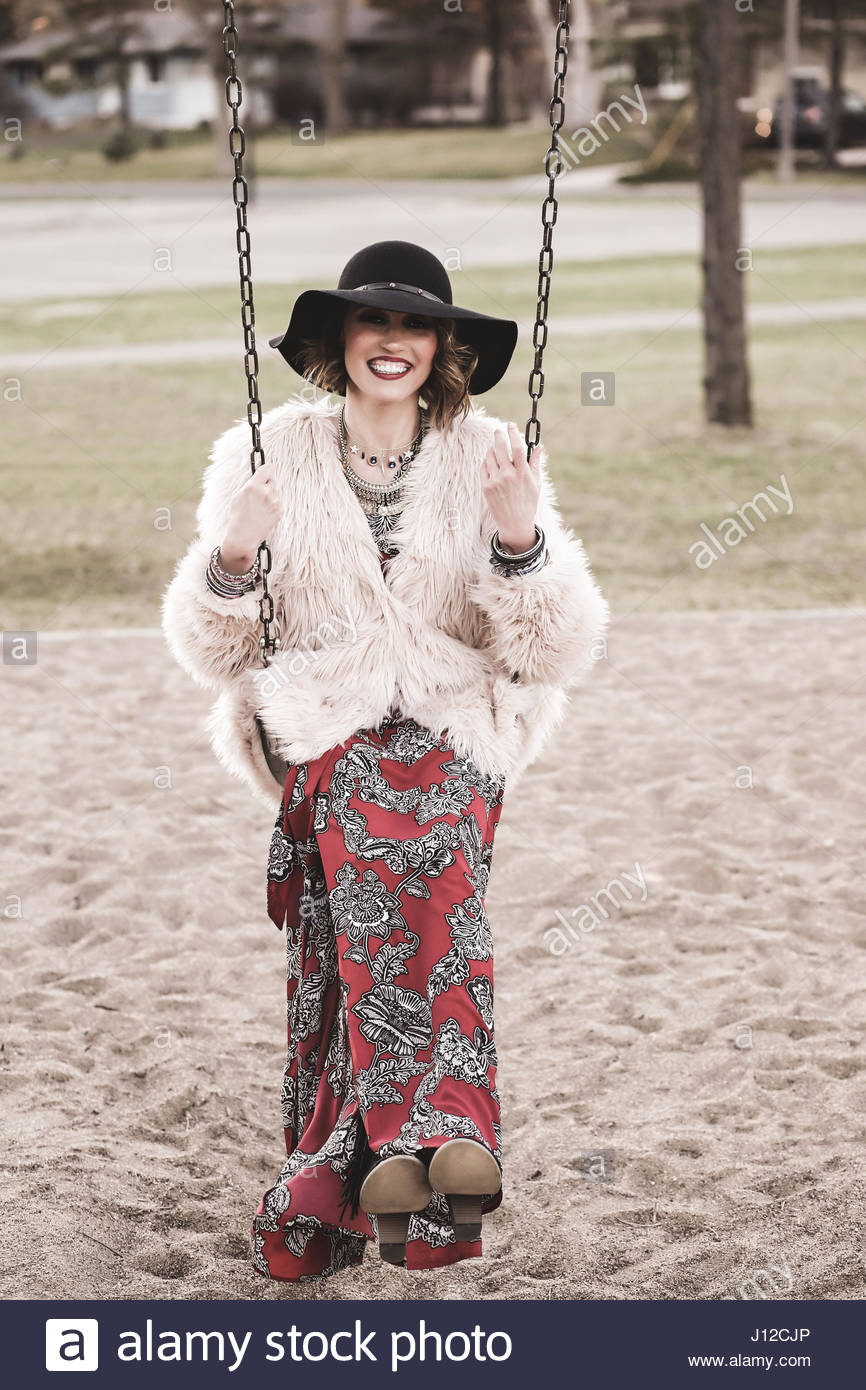 Bohemian dressed woman on a swing - Stock Image