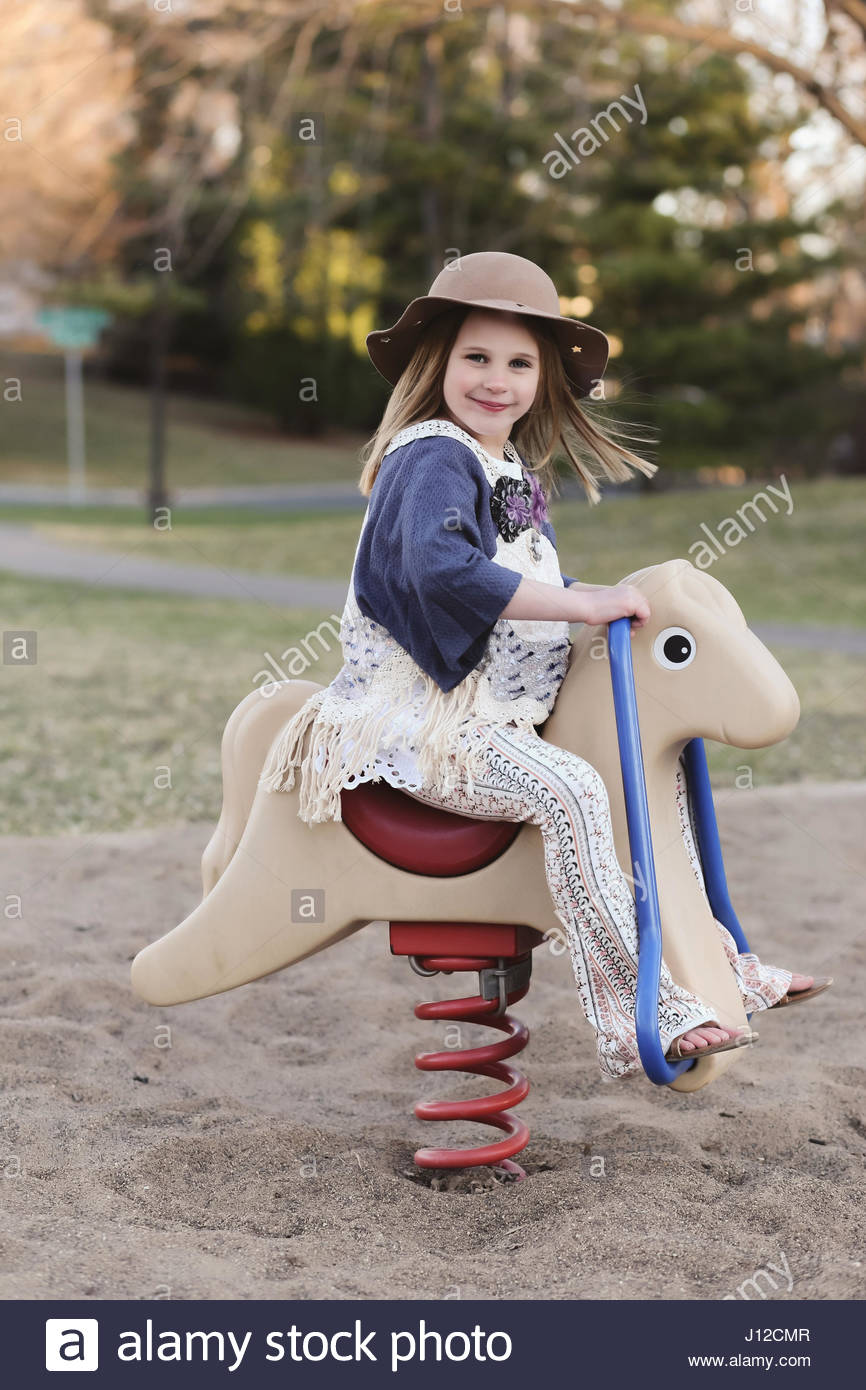 Little girl riding play horse at the park - Stock Image