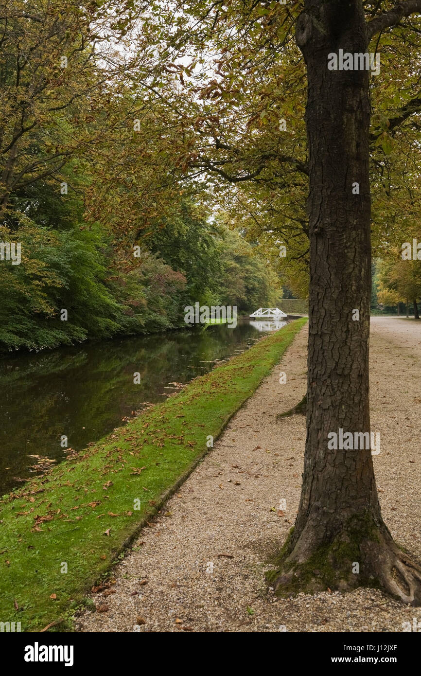 Footbridge over water canal with row of deciduous trees in the Schwetzingen palace garden in late summer, Schwetzingen, - Stock Image