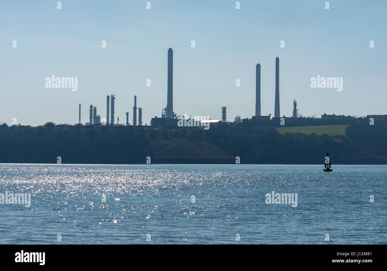 Pembroke refinery seen from across a calm sea on a spring day - Stock Image