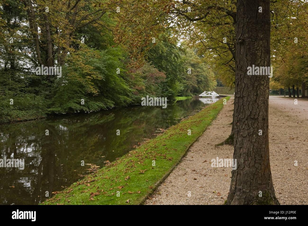 Footbridge over water canal with row of deciduous trees in the Schwetzingen palace garden in late summer, Schwetzingen, - Stock Image